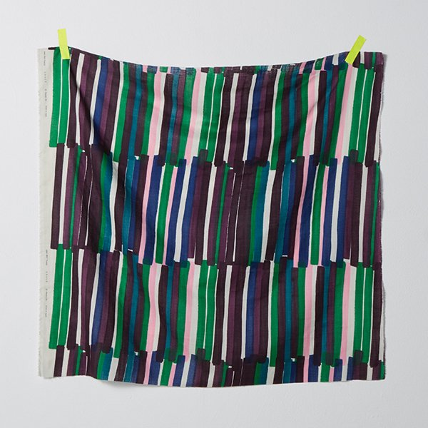 A yard of Nani IRO double gauze fabric hanging on a light gray wall. The fabric has slanted, irregular stripes, about 3cm wide and 30cm long. The stripes are cobalt blue, emeral green, teal, rose pink and shades of purple on a white background.