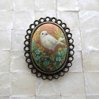 アクセサリー作家 mimeruミメル 身につける絵画【オレンジ背景の鳥×透かしオーバル枠・縦3.5cm】小鳥のブローチ