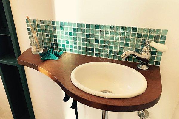 なめらか曲線のカウンターとタイルのおしゃれな手洗い台